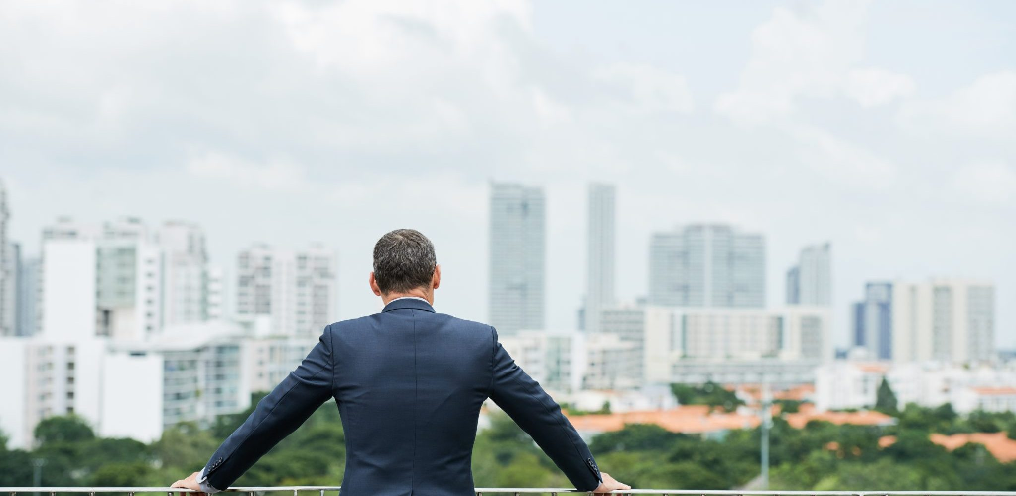 Rear view of company CEO looking at big city from the rooftop